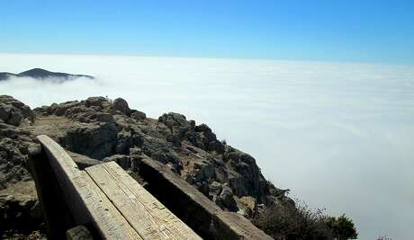 A steep climb up a coastal mountain leads to this lookout bench over the top of the fog deck at Garrapata State Park near Big Sur on the Monterey coast