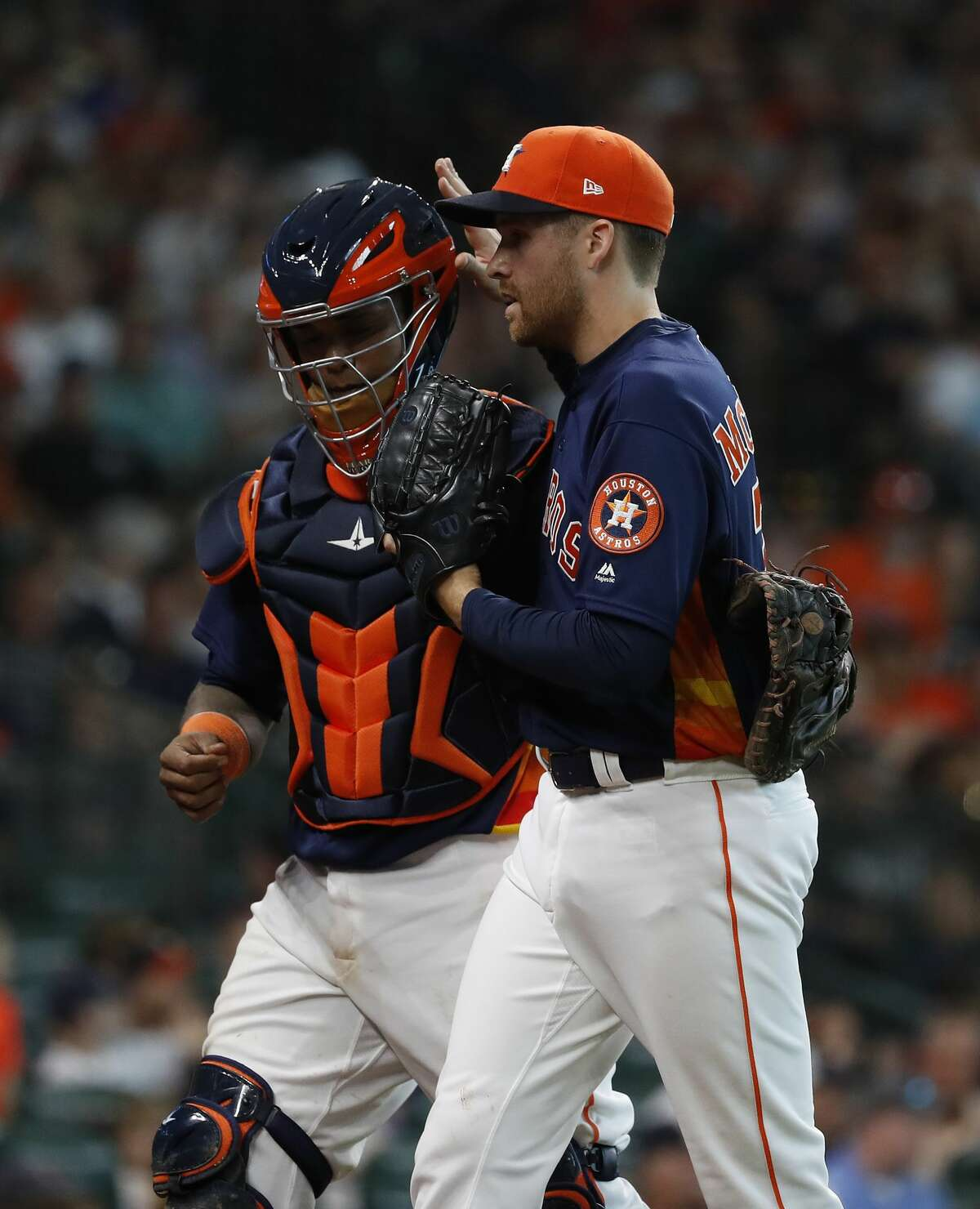 Houston Astros relief pitcher Collin McHugh (31) celebrates with catcher Martin Maldonado (15) after the seventh inning of an MLB game at Minute Maid Park, Sunday, July 29, 2018, in Houston.