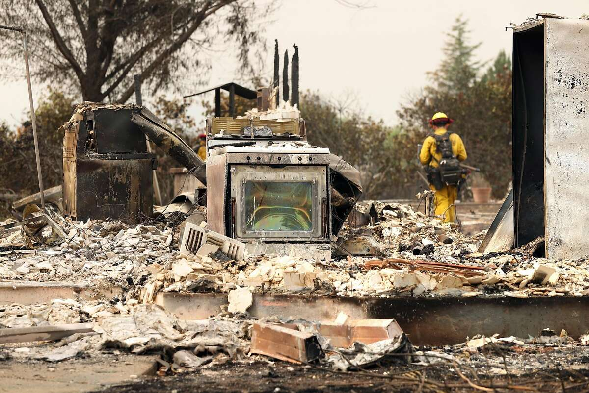 A Cal Fire crew member from San Diego puts out hot spots amongst destroyed houses on Menlo Way in the aftermath of the Carr Fire in Redding, Calif. on Sunday, July 29, 2018.