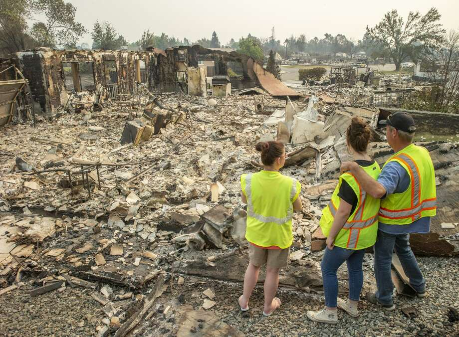 Anna Noland (left), 16-year-old Kailyn Nash and James Nash at their burned home in the Lake Keswick Estates neigh bor hood of Redding. Thousands of firefighters scrambled to push the fire away from the shaken Shasta County town. Photo: Santiago Mejia / The Chronicle / ONLINE_YES