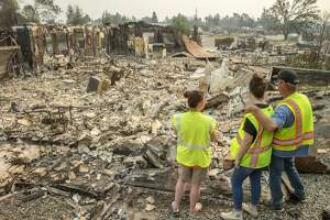Anna Noland (left), 16-year-old Kailyn Nash and James Nash at their burned home in the Lake Keswick Estates neigh bor hood of Redding. Thousands of firefighters scrambled to push the fire away from the shaken Shasta County town.