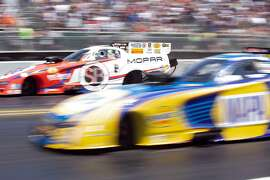 Matt Hagan, left, and Ron Capps run neck and neck in the second round elimination of the championship of the Top Fuel/Funny Car competition of the Toyota NHRA Sonoma Nationals at Sonoma Raceway, on Sunday, July 29, 2018 in Sonoma, Calif.