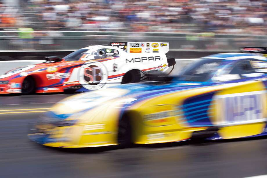 Matt Hagan (left) and Ron Capps run neck and neck in the Top Fuel/Funny Car competition. Photo: D. Ross Cameron / Special To The Chronicle