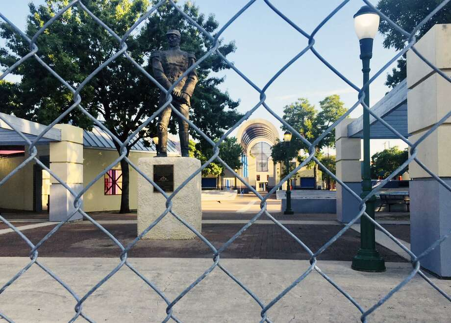 The 6-foot chain-link fence that surrounds Guadalupe Plaza was installed two-years ago. Behind the fence and pictured in the background the plaza's playground sits unused. Photo: Elaine Ayala, Staff Photographer