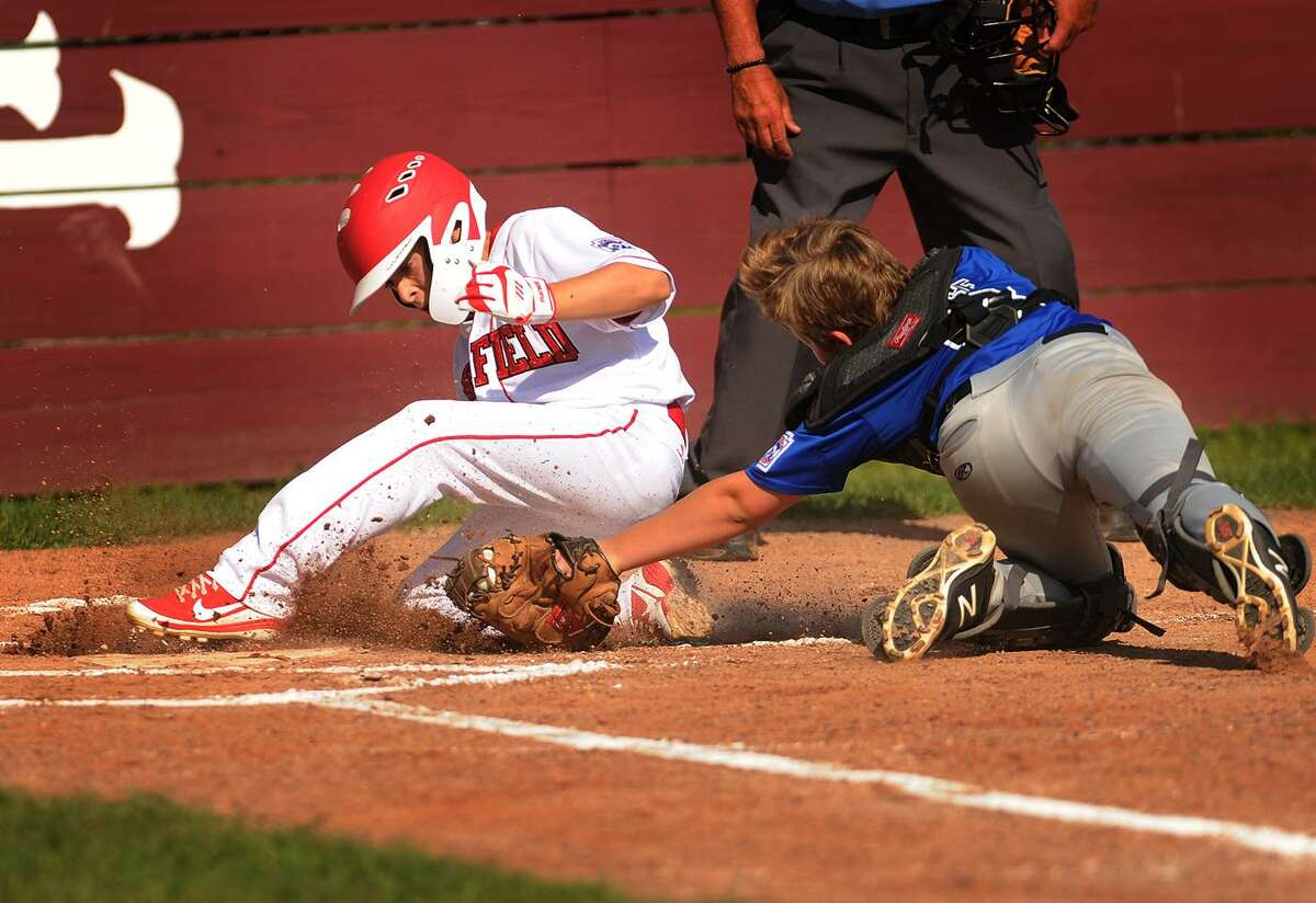 Fairfield American's Jude Gussen slides in safely to home ahead of the tag of Manchester National catcher Easton Masse in the four run second inning of his team's 11-9 victory to win the Little League State Championship at President's Field in East Lyme on Sunday, July 29, 2018.