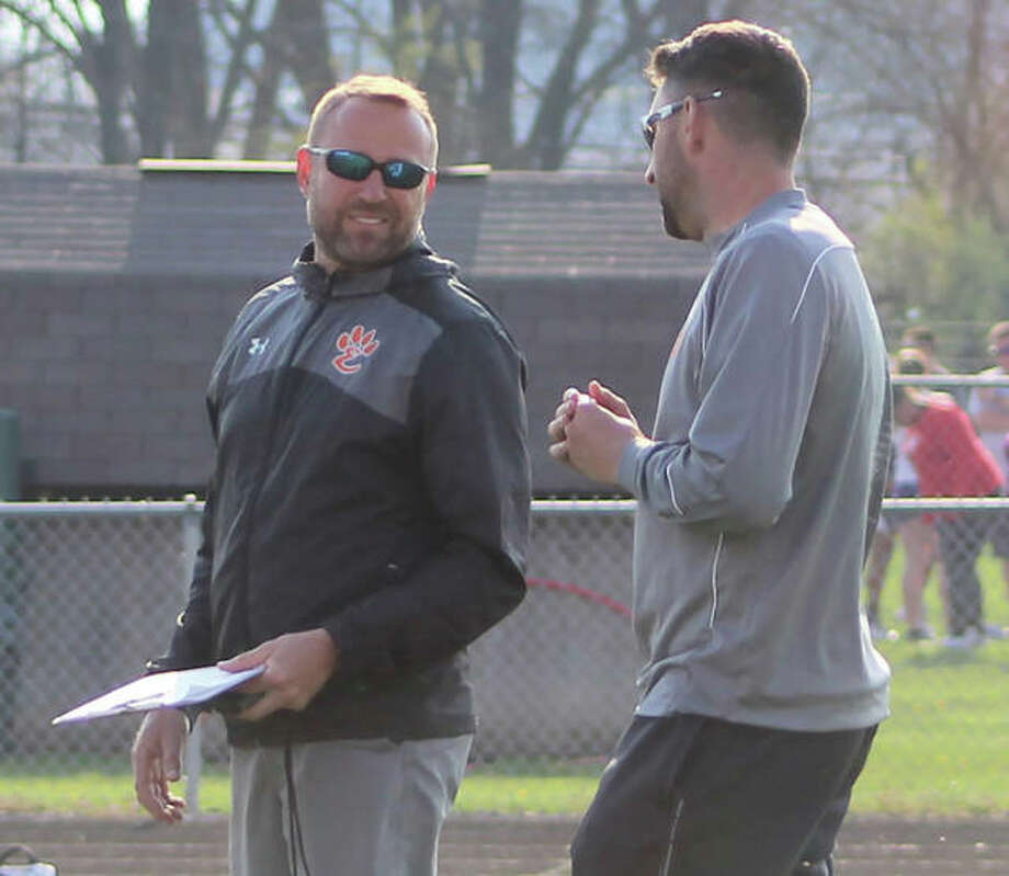 Edwardsville head coach Chad Lakatos (left) talks with Tigers hurdles coach Alex Holler during the Madison County Meet at Highland last season. Lakatos is the 2018 Telegraph Boys Track Coach of the Year. Photo:       Greg Shashack / The Telegraph