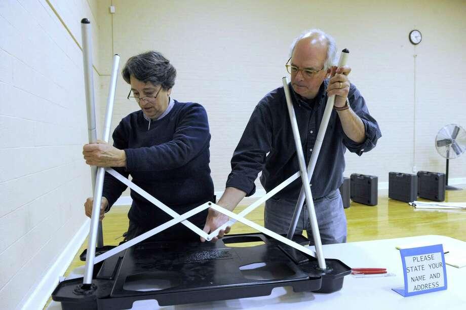 Nancy Ryan, left, Democratic deputy registrar of voters and Tim Beeble, assemble a voting table at the Bethel Municiple Center in Bethel, Conn. Monday, Nov. 3, 2014. Photo: Carol Kaliff / Carol Kaliff / The News-Times