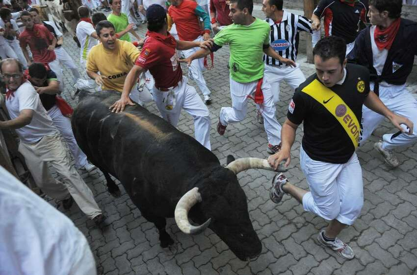 PAMPLONA, SPAIN - JULY 08: People run beside a fighting bull during the second bullrun of the San Fermin fiesta on July 8, 2010 in Pamplona, Spain. Fighting bulls run through the historic heart of Pamplona for eight days in this fiesta made famous by the 1926 novel of U.S. writer Ernest Hemmingway called 'The Sun Also Rises'. > on July 8, 2010 in Pamplona, Spain. (Photo by Denis Doyle/Getty Images)