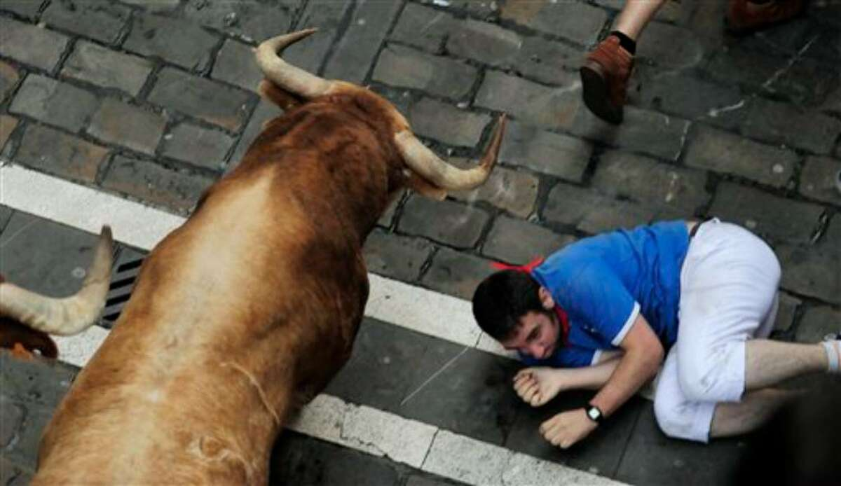 A reveler reacts as a Cebada Gago ranch fighting bulls runs by him during the San Fermin fiestas on Thursday, July 8, 2010, in Pamplona, Spain. (AP Photo/Alvaro Barrientos)