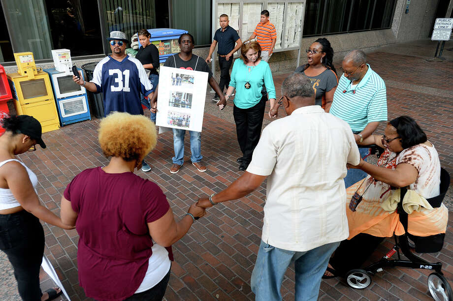 Attendees join hands in prayer during a vigil outside the Jefferson County Courthouse. The vigil was held to pray for an end to violent crime. Photo taken Friday 7/27/18 Ryan Pelham/The Enterprise Photo: Ryan Pelham/The Enterprise / ?2018 The Beaumont Enterprise