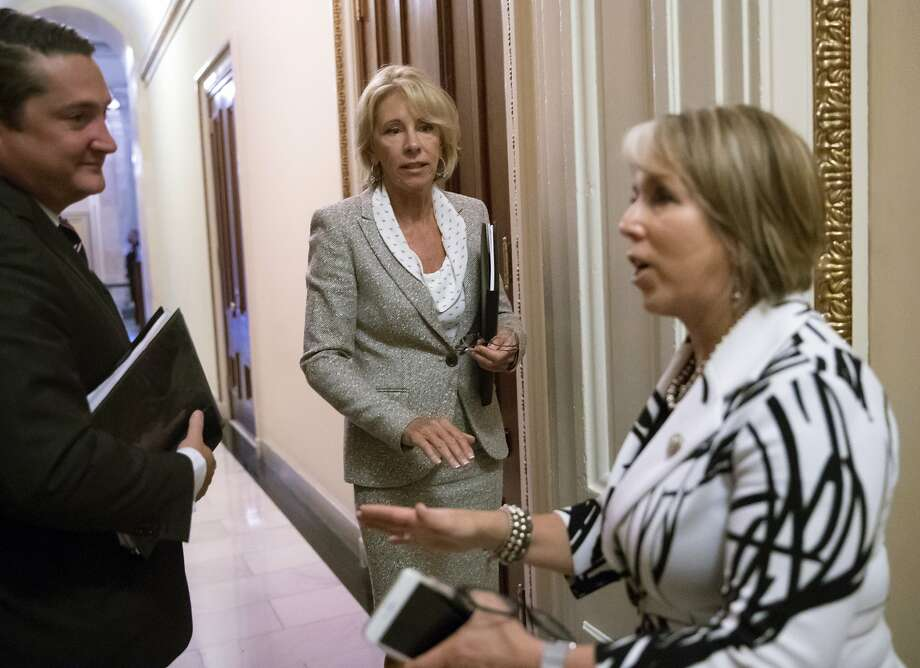 FILE -- Education Secretary Betsy DeVos, center, has a final word with Hispanic Caucus Chair Rep. Michelle Lujan Grisham, D-N.M., right, following a meeting on Capitol Hill in Washington, Thursday, July 26, 2018. Various controversial decisions made by DeVos during her time as secretary of education were referenced in the petition as reasons why James should take her place. Photo: J. Scott Applewhite, Associated Press