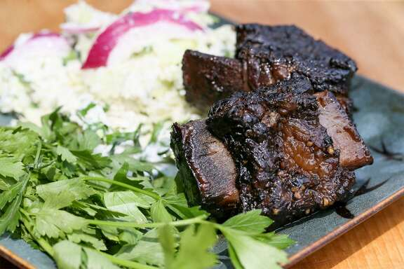Finished smoked beef short ribs braised in a wine sauce served with a side of jalapeño blue cheese coleslaw and garnished with cilantro at Chuck's Food Shack.