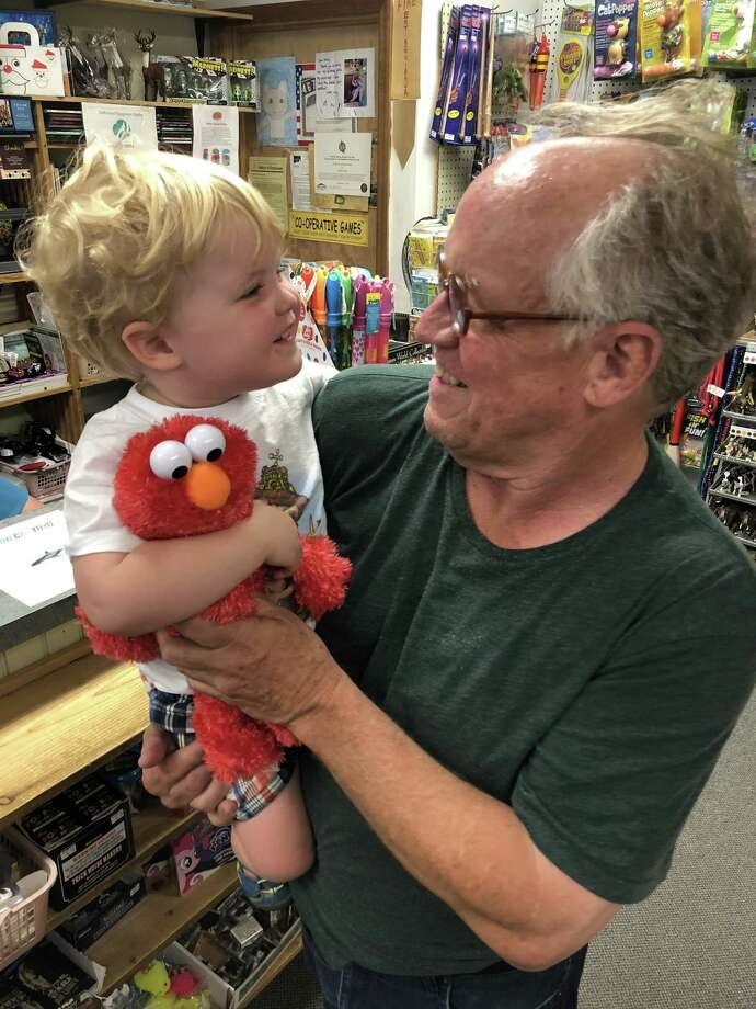 Joe Fitzgerald and his grandson, Owen Fitzgerald Burke, celebrate Owen's first trip to Nordica Toy Store with the purchase of an Elmo stuffed animal. Photo: Deborah Rose / Hearst Connecticut Media / The News-Times  / Spectrum