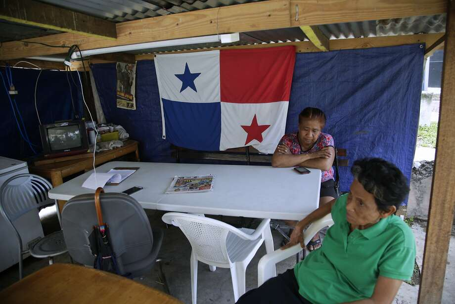 In this May 22, 2018 photo, long-time residents of the Casco Viejo neighborhood sit in a shelter outside the Nicolas Pacheco school where they live with other displaced families after they were forced out of their apartments by owners in Panama City. Locals initially welcomed the UNECSO designation as a UNESCO world heritage site, hoping to reap the benefits of the revitalization that would come, but ended up getting pricing out, as long-absent landowners converted properties to hotels or night spots or rented instead to well-heeled tenants. (AP Photo/Arnulfo Franco) Photo: Arnulfo Franco, Associated Press