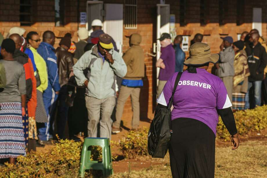An official election observer walks by voters waiting in line to cast their ballots at a polling station in the Kuwadzana township, in Harare, Zimbabwe on July 30, 2018. Photo: Bloomberg Photo By Waldo Swiegers. / © 2018 Bloomberg Finance LP