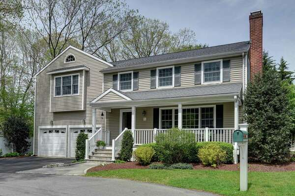 The taupe-colored, updated colonial house at 86 Shadowood Road is on a cul-de-sac in a University neighborhood walking distance to Riverfield Elementary School and Fairfield University.