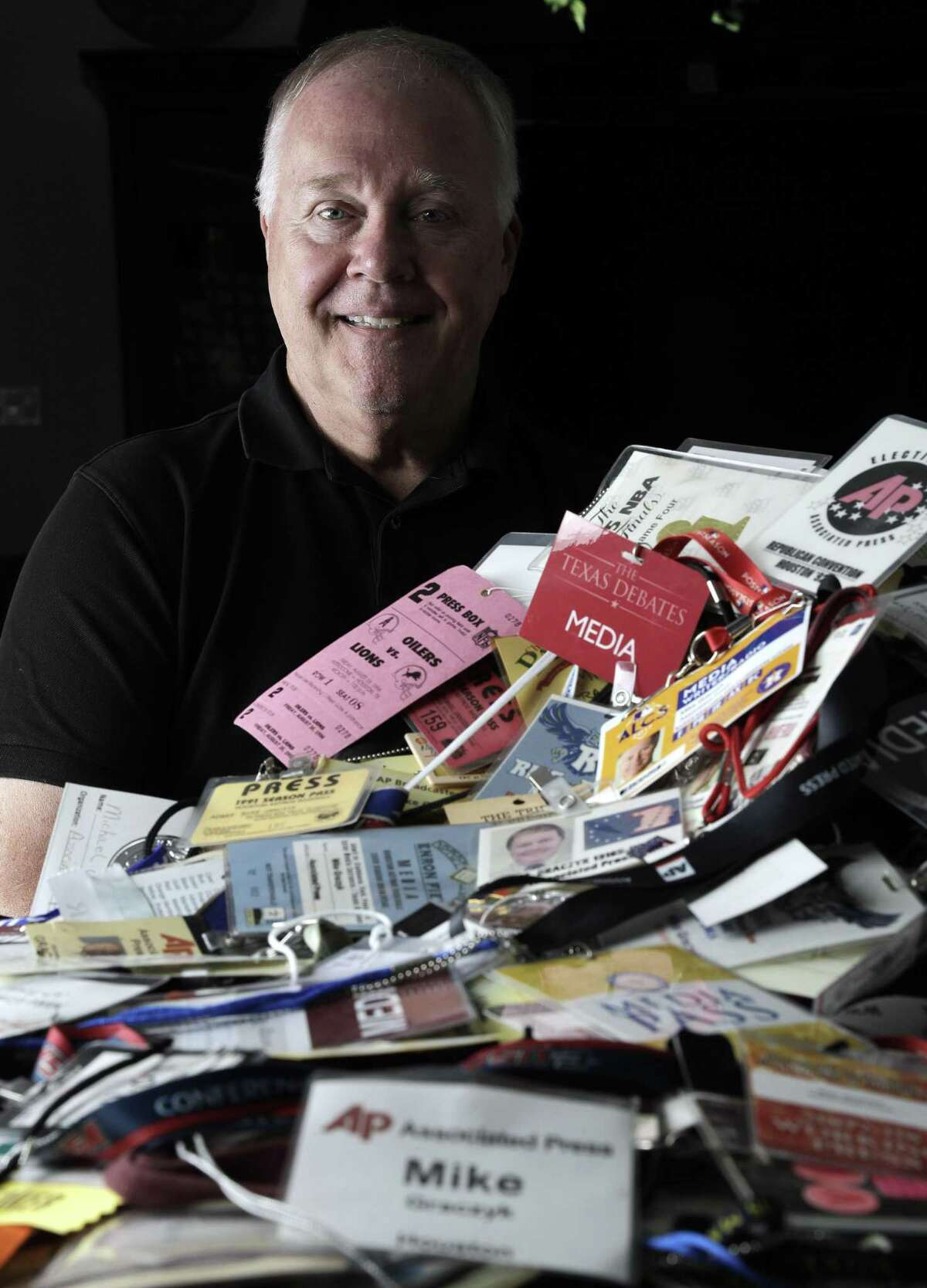 Veteran Associated Press reporter Michael Graczyk poses with some of many media credentials he has been issued over his career with the AP.