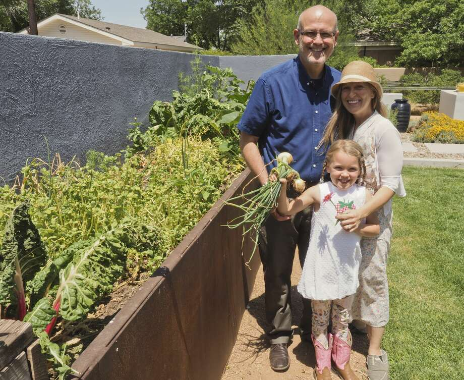 Dr. Staton Awtrey, left, his wife, Blythe, and their daughter, Lillian, check their garden for fresh vegetables on May 31. Photo: Tim Fischer/Midland Reporter-Telegram