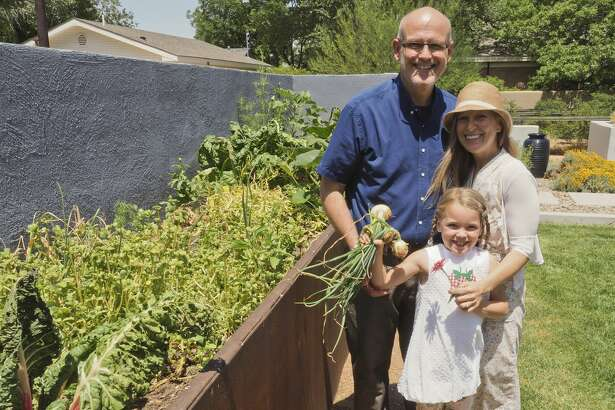Dr. Staton Awtrey, left, his wife, Blythe, and their daughter, Lillian, check their garden for fresh vegetables on May 31.