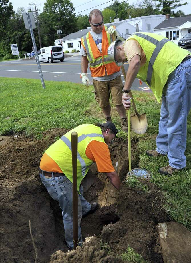 From left, Andrew Kokinchak, Jeff Priano and Project Manager Greg Dembowski, measure the depth of the water main near 777 Federal Road in Brookfield Monday, July 30, 2018. These measurements are necessary to finalize the design on the second phase of the downtown streetscape project, which will include sidewalks, trees and other amenities. Photo: Carol Kaliff / Hearst Connecticut Media / The News-Times