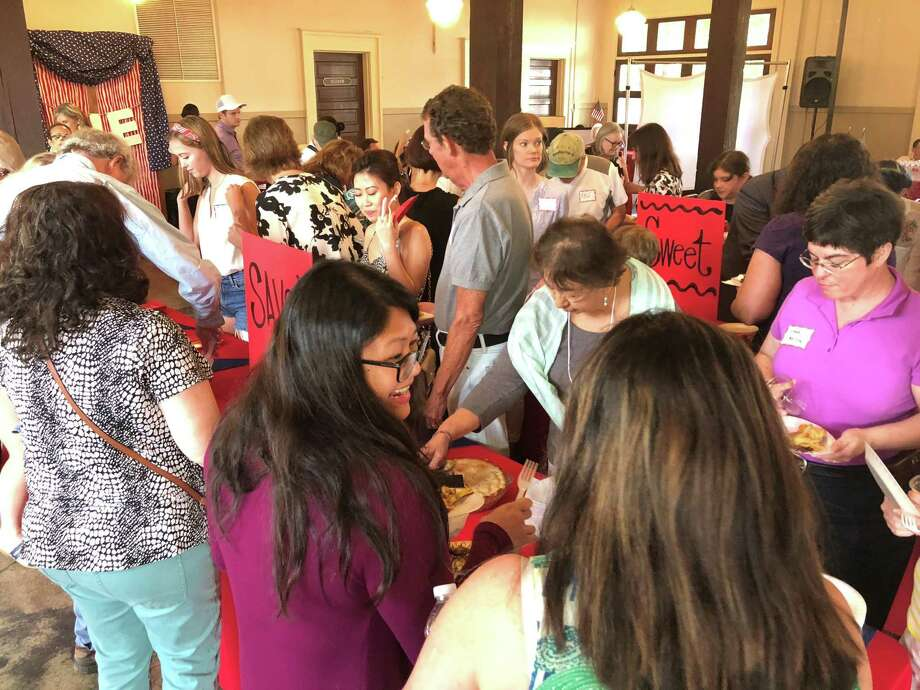 Event attendees and bakers crowd in to sample the different varieties of pie at The Heights Great American Pie Contest held July 9 at the Houston Heights City Hall & Fire Station. Photo: Tracy Maness