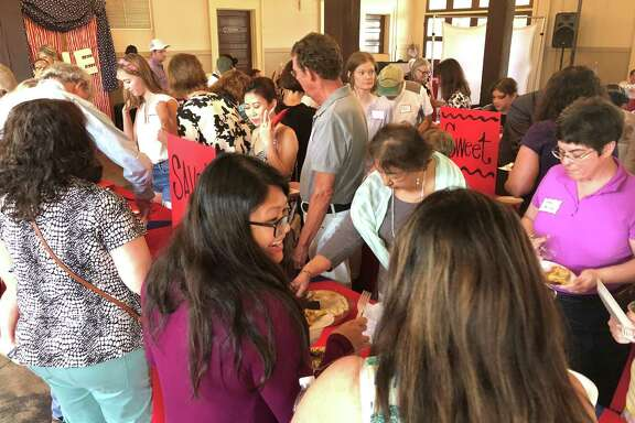Event attendees and bakers crowd in to sample the different varieties of pie at The Heights Great American Pie Contest held July 9 at the Houston Heights City Hall & Fire Station.