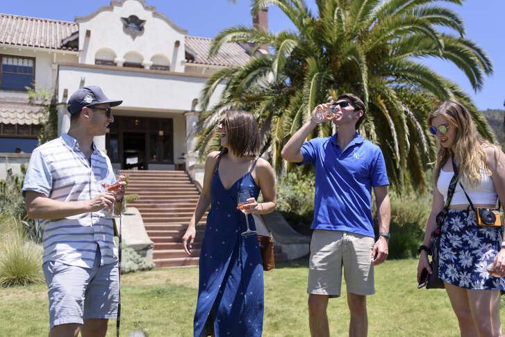 Adam Levine, left, Rachel Holden, Josh Barlow, and Brooke Eliot walk in the grass with their wine glasses in front of the Hacienda House at   Scribe   Winery in Sonoma, Calif., on Saturday June 23, 2018.