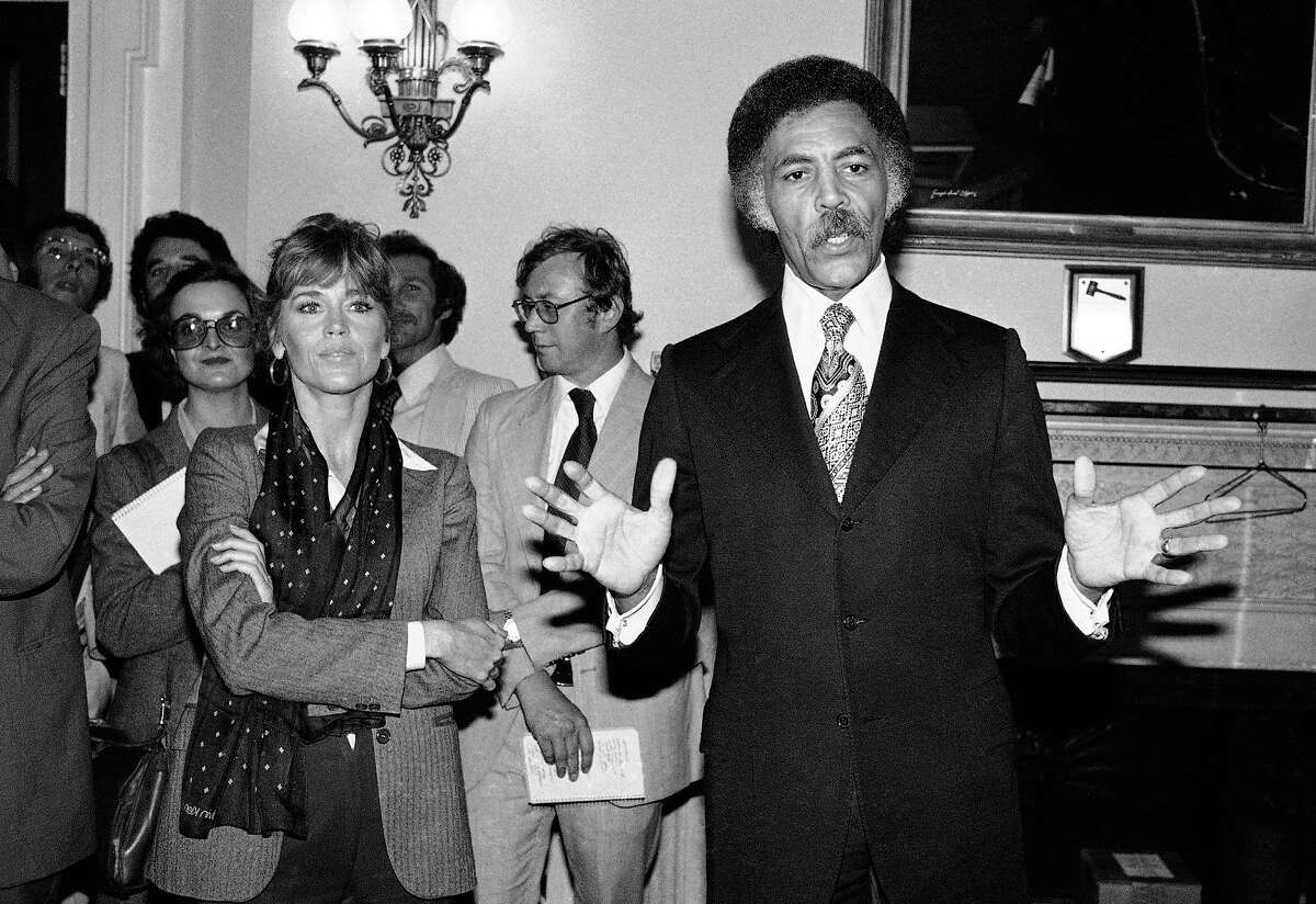 FILE - In this Sept. 26, 1979 file photo Jane Fonda stands beside, Rep. Ronald Dellums, D-Calif., right, in Washington. Dellums, a fiery anti-war activist who championed social justice as Northern California's first black congressman, has died at age 82. Longtime adviser Dan Lindheim says Dellums died early Monday, July 30, 2018, at his home in Washington, D.C., of cancer. (AP Photo/John Duricka, File)