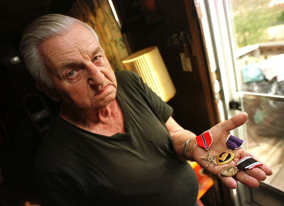 World War II veteran Raymond W. Hudlow holds his Bronze Star, Purple Heart and POW medals Feb. 5, 2001, at his home near Lynchburg, Va. His state labeled him a ``mental defective'' and surgically sterilized him. Years later his state refused to apologize to him an thousands of others who fell victim to eugenics popular at the time. What is happening now that we will have to apologize for? Photo: ANDRES R. ALONSO /AP / AP