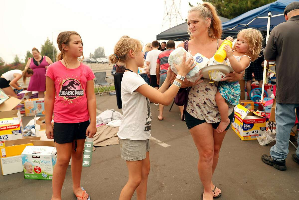 Carr Fire evacuee Holly Mason holds her 2-year-old daughter as she joins her other two daughters Kendra, 8, and McKayla, 9, (left) in picking supplies at a community organized aid station at Mt. Shasta Mall.