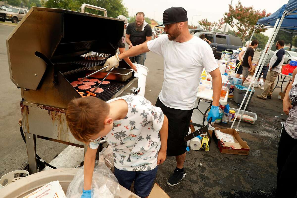 Raymond Brown and his son, Austin, make hot dogs and hamburgers for evacuees in the Mt. Shasta Mall parking lot in Redding on July 30, 2018.