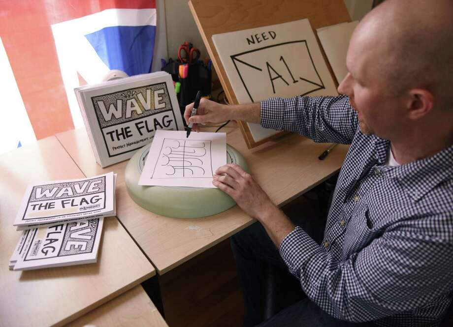 "Whitby School design teacher Phil Lohmeyer sketches a sample design beside his new book, ""Wave the Flag,"" at his home in the Shippan neighborhood of Stamford on Thursday. Photo: Tyler Sizemore / Hearst Connecticut Media / Greenwich Time"