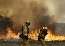 Firefighters with Cal Fire Mendocino Unit work the line as a wildfire advances Monday, July 30, 2018, in Lakeport, Calif. A pair of wildfires that prompted evacuation orders for thousands of people are barreling toward small lake towns in Northern California. (AP Photo/Marcio Jose Sanchez)