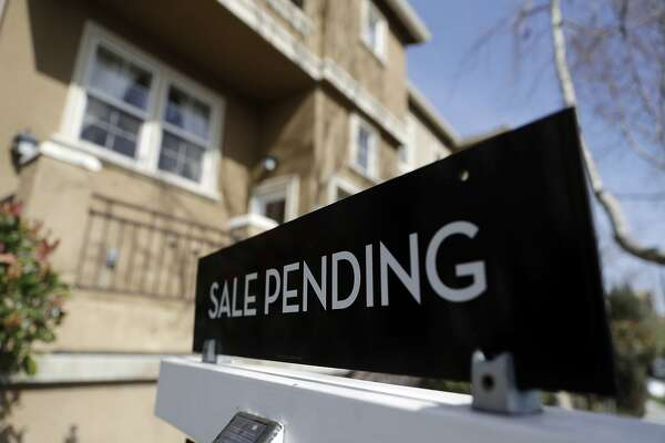 FILE - In this March 6, 2018, photo a sign advertises the pending sale of a home in San Jose, Calif. More Americans signed contracts to purchase homes in June compared to May, but the volume of pending sales has slipped over the past year. The National Association of Realtors said Monday, July 30, that its pending home sales index rose 0.9 percent last month to 106.9. But on a yearly basis, pending home sales have fallen 2.5 percent. (AP Photo/Marcio Jose Sanchez, File)