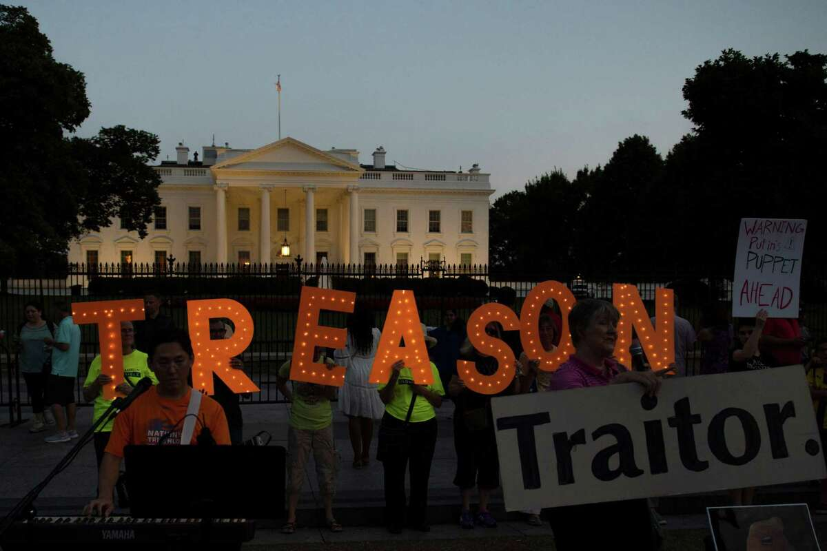 """Activists hold letters reading the word """"Treason"""" in front of the White House during a sunset demonstration to denounce the link between the 2016 Trump campaign and Russia on July 29, 2018 in Washington DC. Trump's former lawyer, Michael Cohen, says he can testify that Donald Trump both knew in advance and approved of the June 9, 2016, meeting at Trump Tower between his campaign's high command and Kremlin emissaries who promised dirt on Hillary Clinton. / AFP PHOTO / Eric BARADATERIC BARADAT/AFP/Getty Images"""