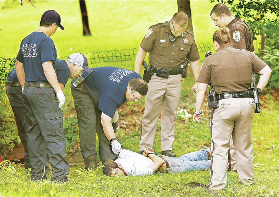 Alton Fire Department Capt. Brian Evans checks on a man who was Tasered by Madison County Sheriff's deputies in the backyard of a house Monday in the 1600 block of Main Street in Alton. Photo:       John Badman | The Telegraph