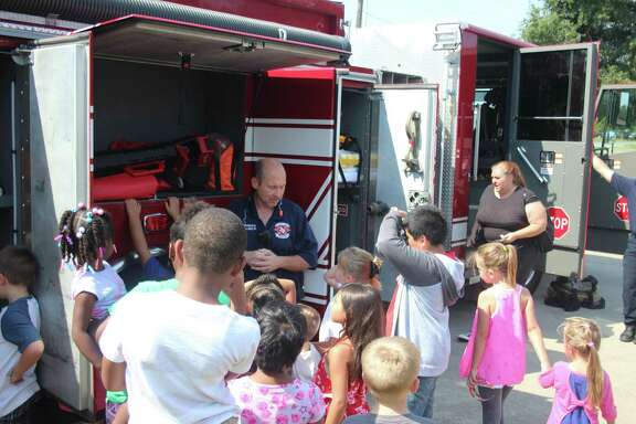 Doug Castleberry of the Cleveland Fire Department displays a variety of firefighting equipment to show to children from the Breech Learning Academy.