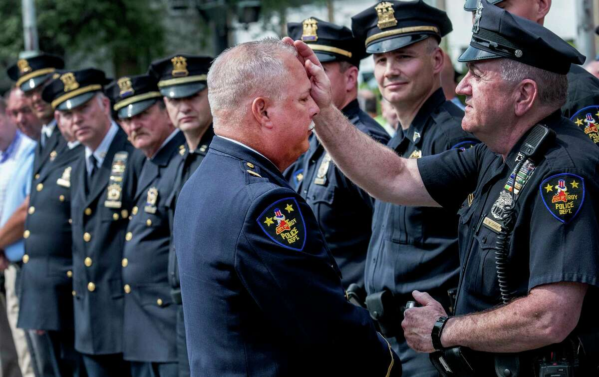 Captain Rick Sprague receives a blessing from lay priest Paul Carney after his retirement ceremony Monday July 30, 2018 in Troy, N.Y. Sprague was a 40 veteran of the Troy Police and commanded the Detective Division and the Emergency Response Team. (Skip Dickstein/Times Union)