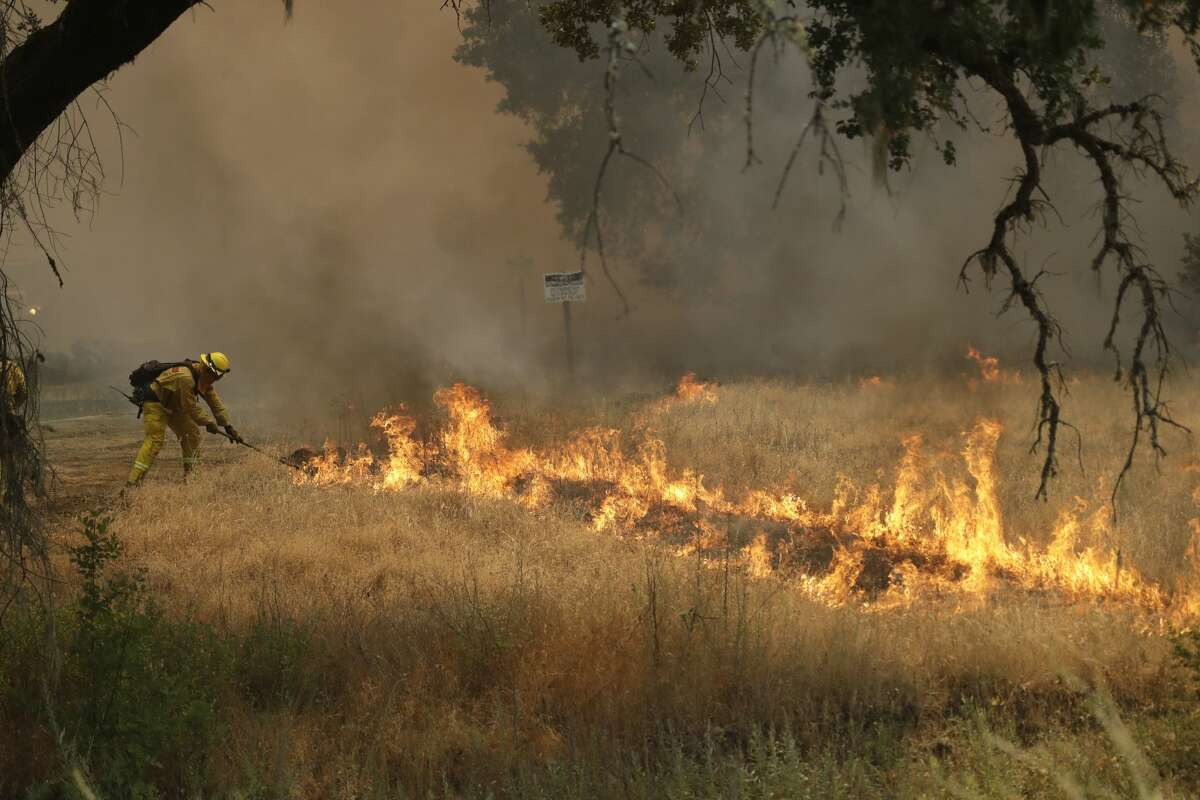 A firefighter with Cal Fire Mendocino Unit takes a rake to flames as a wildfire advances Monday, July 30, 2018, in Lakeport, Calif.