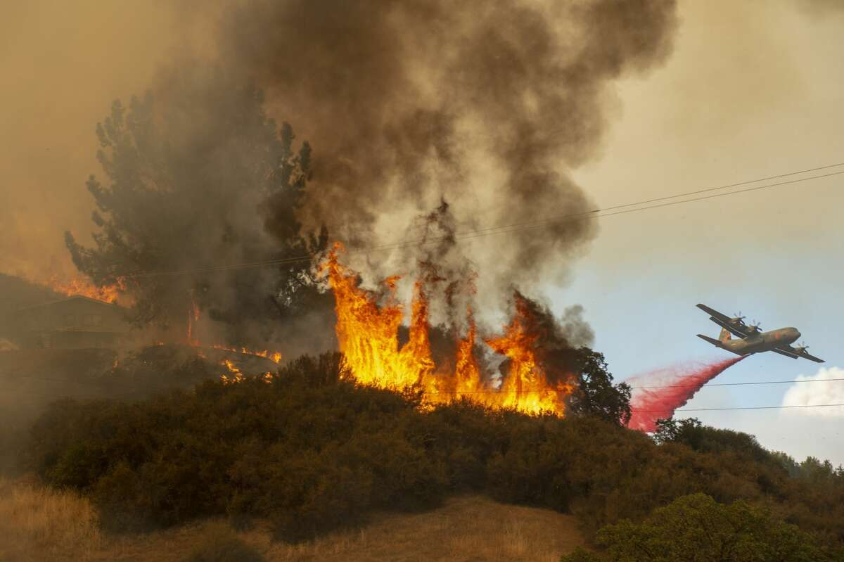 Fire retardant is dropped near a home as a wildfire burns just west of Lakeport, Calif., Monday, July 30, 2018.