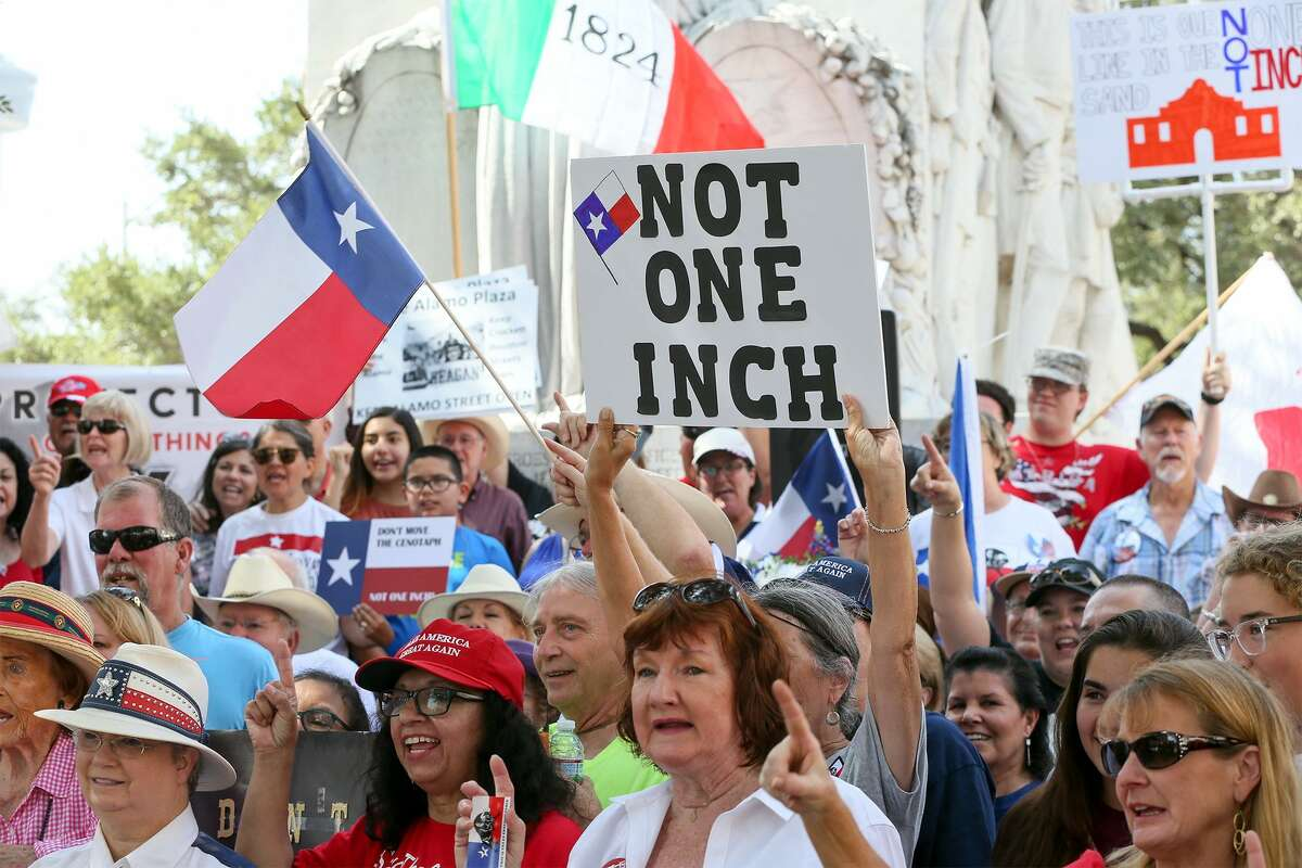 People display signs and flags during a rally opposing relocation of the Cenotaph in Alamo Plaza hosted by the Alamo Defenders Descendants Association on Saturday, July 28, 2018.