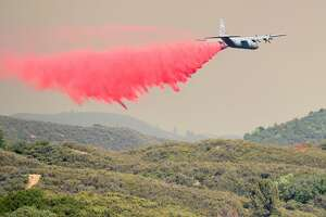An air tanker drops retardant on a hillside ahead of the Mendocino Complex fire near Finley, California on July 30, 2018.  Thousands of firefighters in California made some progress against several large-scale blazes that have turned close to 200,000 acres into an ashen wasteland, destroyed expensive homes, and killed eight fire personnel and civilians in the most populous US state. The worst blaze, northern California's Carr Fire, has killed six people since Thursday, including a 70-year-old woman and her two great-grandchildren aged four and five. They perished when flames swallowed their home in Redding.  / AFP PHOTO / JOSH EDELSONJOSH EDELSON/AFP/Getty Images