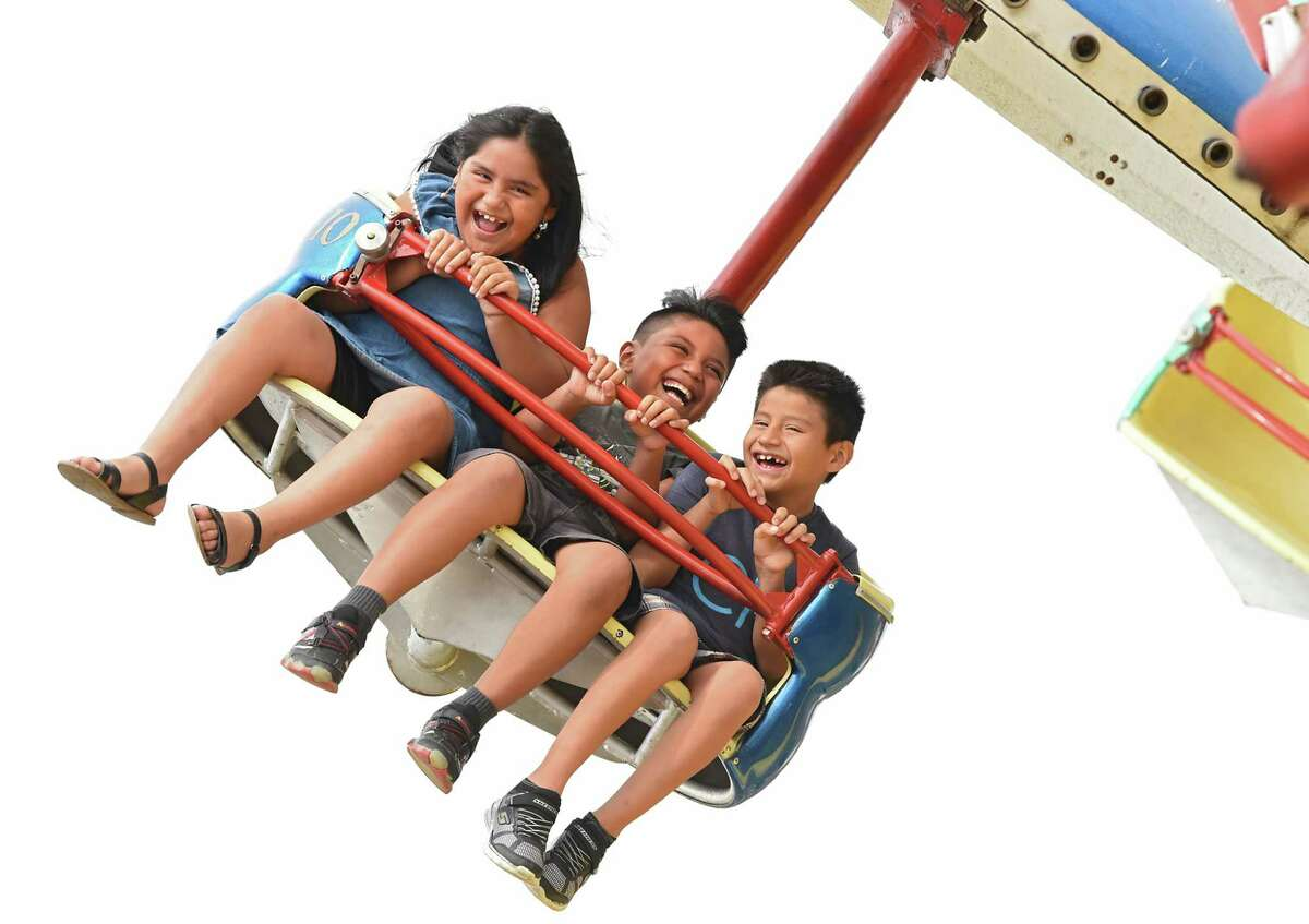Katherine Barros, 8, left, enjoys the thrill of the Paratrooper ride with her brothers Johan, 8, center, and Luis, 9, at Huck Finn's Playland on Monday, July 30, 2018 in Albany, N.Y. The siblings were up from Queens visiting relatives. (Lori Van Buren/Times Union)