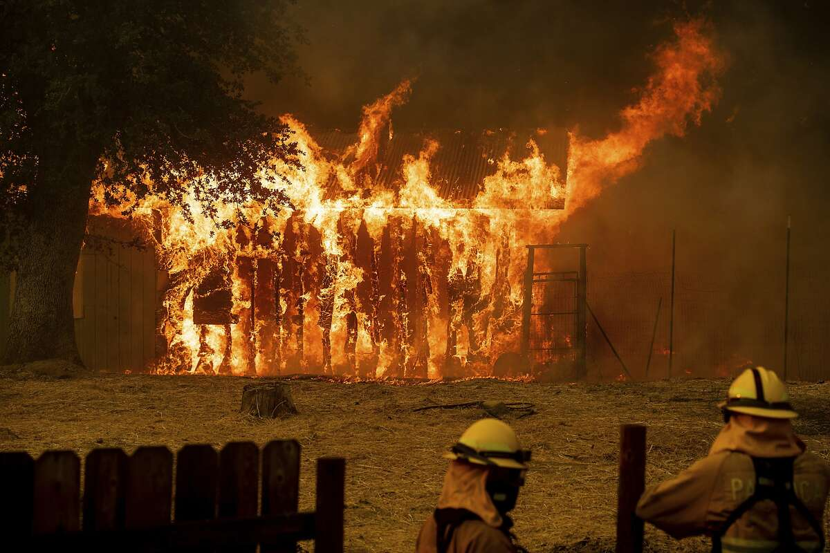 Firefighters monitor a burning outbuilding to ensure flames don't spread as the River Fire burns in Lakeport, Calif., on Monday, July 30, 2018. A pair of wildfires that prompted evacuation orders for nearly 20,000 people barreled Monday toward small lake towns in Northern California, and authorities faced questions about how quickly they warned residents about the wildfires. (AP Photo/Noah Berger)