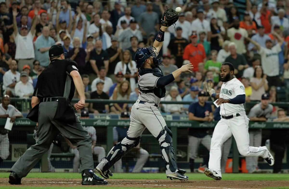Houston Astros catcher Max Stassi reaches for the throw but Seattle Mariners' Denard Span, right, was able to slide and avoid the tag to score a run during the sixth inning of a baseball game, Monday, July 30, 2018, in Seattle. (AP Photo/Ted S. Warren)
