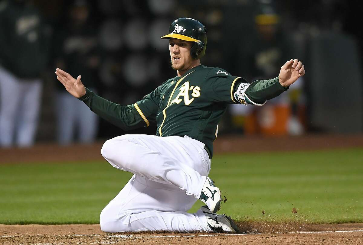 Stephen Piscotty #25 of the Oakland Athletics scores on a sacrifice fly from Jonathan Lucroy #21 against the Toronto Blue Jays in the bottom of the fourth inning at Oakland Alameda Coliseum on July 30, 2018 in Oakland, California.