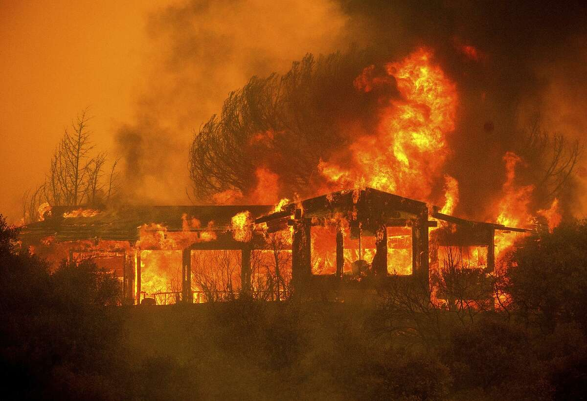 A home burns as the River Fire rages near Finley, between Lakeport and Kelseyville in Lake County, on Monday night.