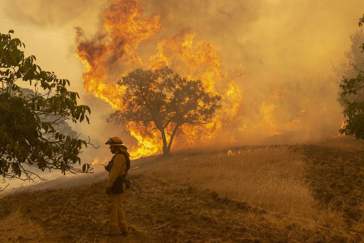 Firefighter Wyatt Belden from Gold Ridge Fire Protection District in Sonoma County monitors a fire burning west of Lakeport.