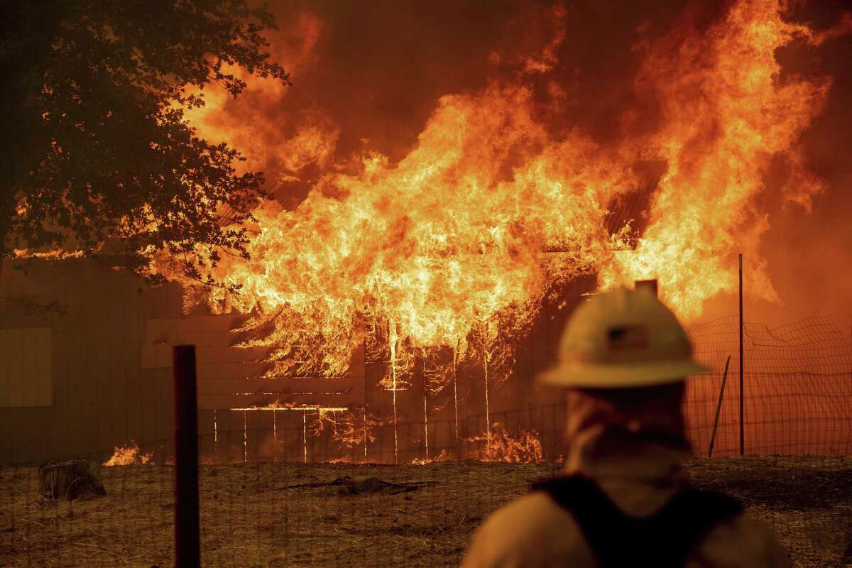A firefighter monitors a burning outbuilding to ensure flames don't spread as the River Fire burns in Lakeport, Calif., on Monday, July 30, 2018. A pair of wildfires that prompted evacuation orders for nearly 20,000 people barreled Monday toward small lake towns in Northern California, and authorities faced questions about how quickly they warned residents about the wildfires.