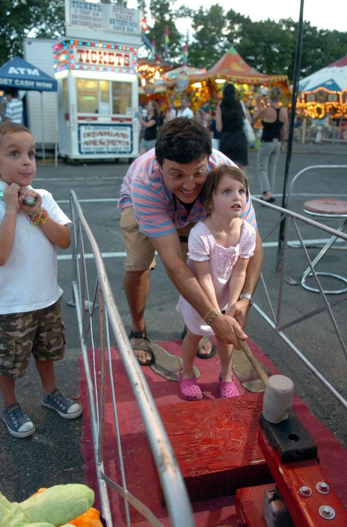Highlights from the 27th Annual Festival Italiano in Westport, Conn. on Thursday July 08, 2010. matt Spengler, of Fairfield, helps his daughter Caroline, 4, with the hammer so she could hit the bell and win a prize. At left is Matt's son James, 5.